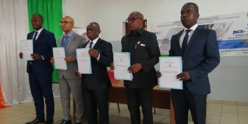 En présence du ministre Kouadio Konan Bertin, les candidats ont signé une charte de bonne conduite et de non-violence qu'ils tiennent sur la photo. (DR)